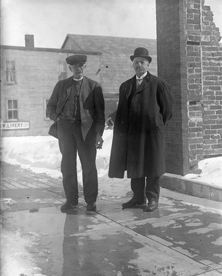 Photograph of two men standing near a livery business, Colborne, Cramahe Township
