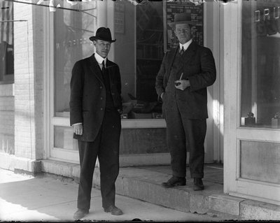 Photograph of Frank Griffis and an unidentified man standing in front of W. F. Griffis Drug Store, King Street East, Colborne