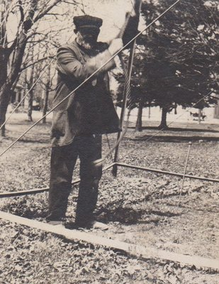 Photograph of a man, possibly James Bawden or George Usborne, pulling the rope of the town bell, Victoria Park, Colborne