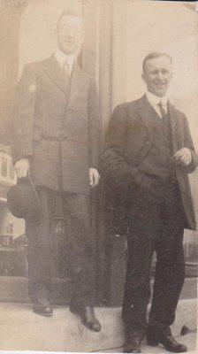 Postcard of two men standing in a doorway, possibly Standard Bank, Colborne