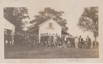 Postcard of a group of men outside a house