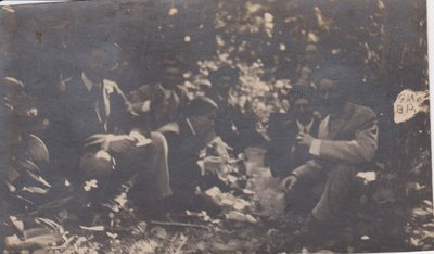 Postcard of a group of men in the woods, inscribed with Gertie Mikle's initials