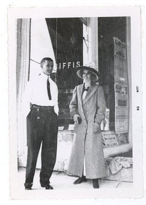 Photograph of an unidentified woman and man standing in front of Griffis drug store, 1910s, Colborne Women's Institute Scrapbook