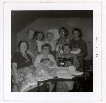 Photograph of Marjorie Rutherford, Goldie Cox, Maggie Mackie, Maizie Cockburn, Amy Gresham, Flossie Pebbles, Hattie McLaughlin and Ellen MacGregor, Colborne Women's Institute Scrapbook