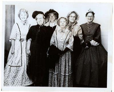 Photograph of Amy Gresham, Maggie Mackie, Ellen MacGregor, Grace Corbyn, Kate Thompson and Gertrude Bradford at Tweedsmuir tea fundraiser, Colborne Women's Institute Scrapbook