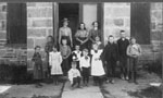 Children and three women in front of Stone School at Henderson's Corners.