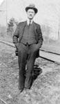 Man standing beside a rail line.