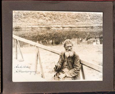 Elderly man sits on a bridge in Kharkiv, begging