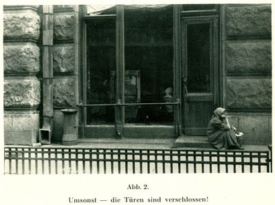 A woman sits on the doorstep of an unidentified establishment in Kharkiv