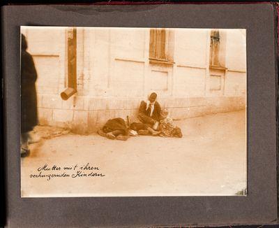 Mother sitting on a sidewalk in Kharkiv, feeds her starving children