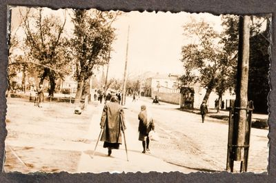 A woman on crutches and a young girl walk down a residential street in Kharkiv
