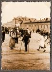 Many people milling about on a broad city street or square in Kharkiv, with two women and a man leaning on crutches in the foreground