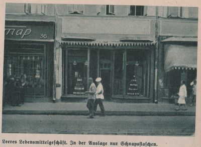 Two men walk by a store in Kharkiv with liquor bottles displayed in the window