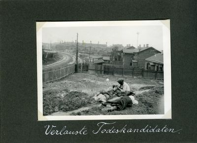 Three women resting on a grassy plot near some houses and a factory in Kharkiv