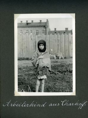 A thin young girl faces the camera as she stands near a factory in Kharkiv