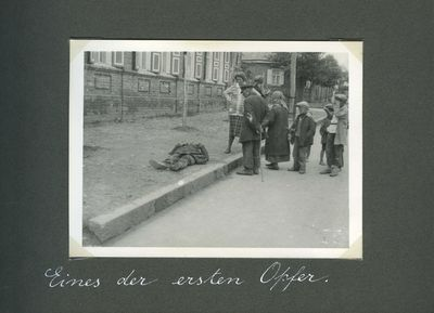 Small group of people gathers around a famine victim lying dead on a sidewalk in Kharkiv