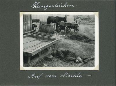 A farm woman, victim of starvation, lies behind a cart near a marketplace in Kharkiv