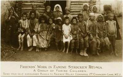 Non-Holodomor: Large number of children pose in front of a small log building in Russia