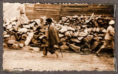A barefoot young man on crutches walks past a pile of stone rubble on a street in Kharkiv