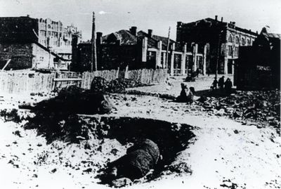 A person lies in a partially excavated area in Kharkiv with old factory buildings in the background