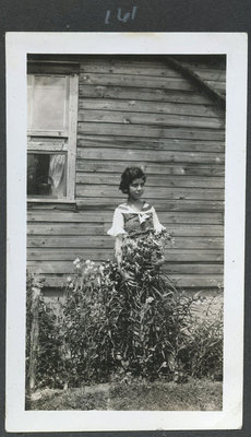 Photo of a young girl standing in a flowerbed beside a house.