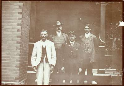 W.H. (William Henry) Schmalz and a group of unidentified men on the steps of his home