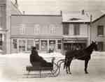 Man in horse-drawn sleigh on King St., Waterloo, Ontario