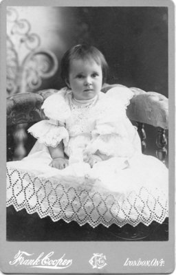 Unidentified girl in a beautiful gown, seated in a chair, London, Ontario