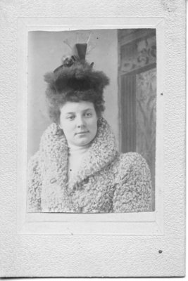 Portrait of an unidentified young woman in a persian wool coat wearing a fur and feather hat, London, Ontario