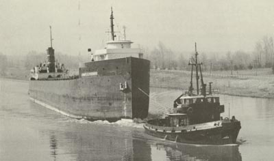 JAMES E. FERRIS is towed through the Homer Bridge by SALVAGE MONARCH and HELEN M. McALLISTER.