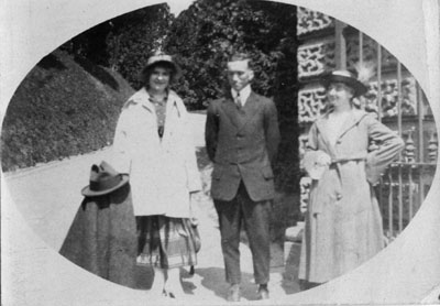 Man and two women standing by building