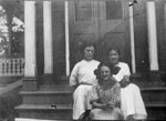 Three women sitting on steps of porch