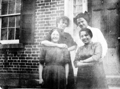 Four women posed in front of door