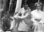 Two women sitting on steps of porch