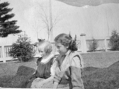 Woman and young girl seated on grass