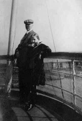 Man and girl posed on rail of ship