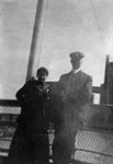 Man and young lady posed on rail of ship