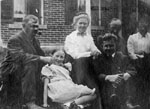 Family group of six seated in front of brick house