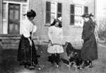 Three young women and dog engaged in croquet game