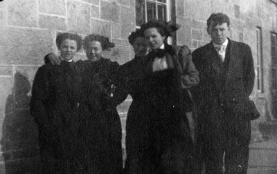 Four women and one man posed outside stone building