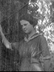 Young lady posed by tree