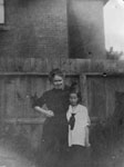 Woman and young girl standing by fence