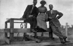 Two men and a woman sitting on railing