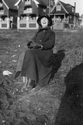 Woman seated in front of row of houses