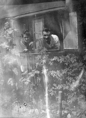 Man and woman leaning through cottage window