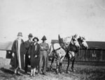 Two men and two women posed with horses
