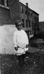 Young child posed in front of basement of building