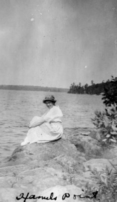 Lady sitting on a rock by a lake