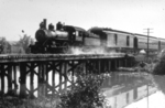 Steam train crossing a wooden trestle bridge