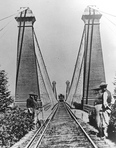 Railway Suspension Bridge workers and train in the distance